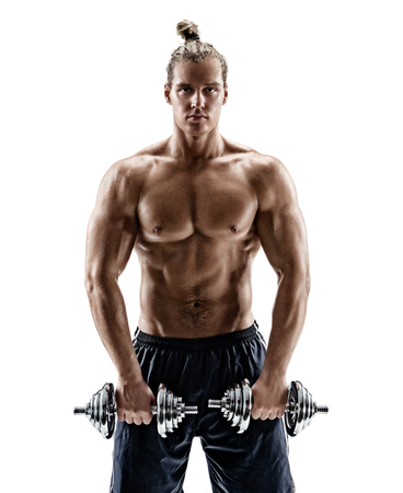 Handsome bodybuilder doing the exercises with dumbbells. Photo of muscular male shirtless isolated on white background. Strength and motivation
