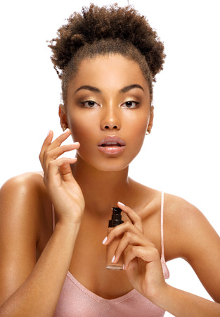 Beautiful woman applying tone cream on her face. Photo of young african american woman on white background. Skin care and beauty concept