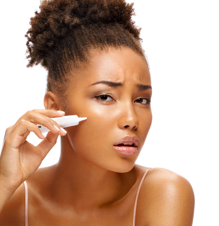 Scowling girl applying treatment cream. Photo of african american girl on white background. Skin care and beauty concept Reklamní fotografie