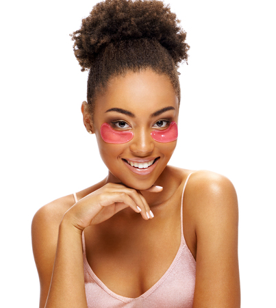 Smiling girl with pink eye patches on her face. Photo of african american girl touching her flawless skin on white background. Skin care concept