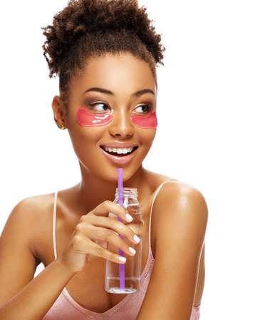 Beautiful girl with pink eye patches on her face and holds bottle of clean water. Photo of young african american girl isolated on white background. Youth and Beauty Reklamní fotografie