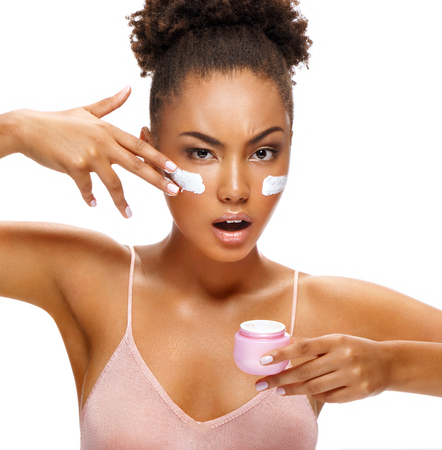 Resolute woman applying moisturizer cream on her face. Photo of beautiful african american woman with flawless skin on white background. Skin care concept