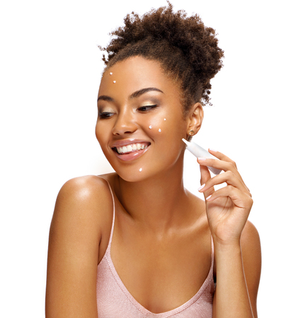 Happy girl applying treatment cream. Photo of smiling african american girl isolated on white background. Skin care concept Reklamní fotografie