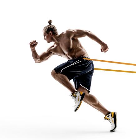 Corredor de hombre deportivo en silueta con una banda de resistencia en su rutina de ejercicios. Foto de joven descamisado aislado sobre fondo blanco. Movimiento dinámico. Vista lateral. Longitud total