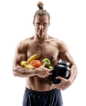 Resting time. Handsome muscular man holding fresh fruits and big jar of sports nutrition isolated on white background. Organic food and health concept 免版税图像