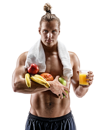 Resting time. Handsome muscular man with towel on shoulders holding fresh fruits and orange juice on white background. Organic food and health concept Stockfoto