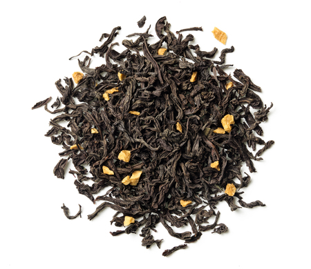 Black tea with passion fruit pieces on white background. Top view. Close up. High resolution