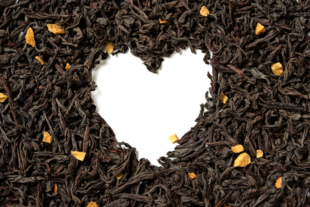 Heart shaped from black tea with passion fruit pieces on white background. Top view. Close up. High resolution 스톡 콘텐츠