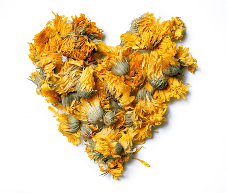 Heart shaped from medicinal flowers of a calendula isolated on white background. Herbal tea. Top view. Close up. High resolution Standard-Bild - 119138403