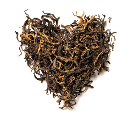 Heart shaped from black tea isolated on white background. Top view. Close up. High resolution Banco de Imagens