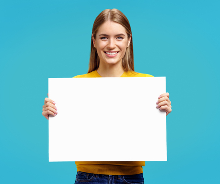 Smiling girl with white empty poster on blue background. Copy space for your text.