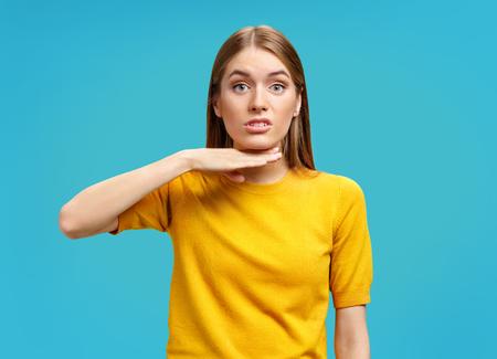 Ich habe es satt. Wütendes junges Mädchen in gelbem Pullover, das ihren Hals mit der Hand berührt und auf blauem Hintergrund eine Grimasse verzieht