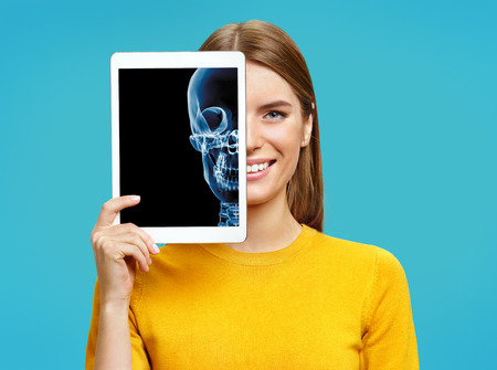 Girl shows X-ray of the skull. Photo of young girl with tablet in her hands on blue background. Medical concept