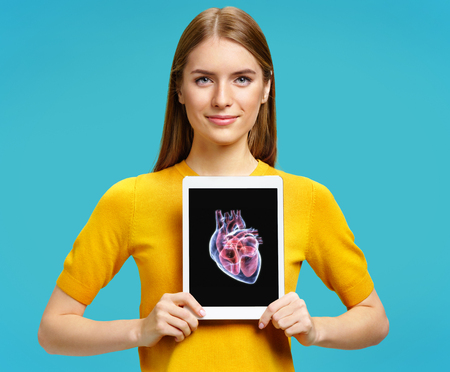 Girl shows the x-ray image of the heart. Photo of young girl with tablet in her hands on blue background. Medical concept