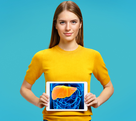 Girl shows the x-ray image of the liver. Photo of young girl with tablet in her hands on blue background. Medical concept Banque d'images - 119607670