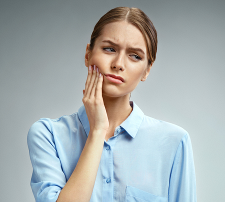 Woman suffering from annoying strong teeth pain. Photo of american woman in blue shirt on gray background. Medical concept