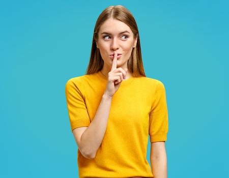 Behalte mein Geheimnis! Schönes junges Mädchen, das Finger auf Lippen hält und Stillegeste zeigt. Foto des Mädchens sieht im gelben Pullover auf blauem Hintergrund mysteriös beiseite.