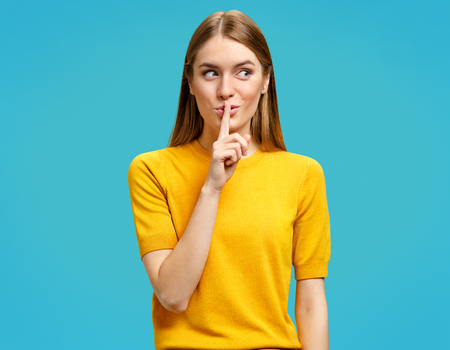 Keep my secret! Beautiful young girl holding finger on lips and showing silence gesture. Photo of girl looks mysteriously aside in yellow sweater on blue background. Standard-Bild