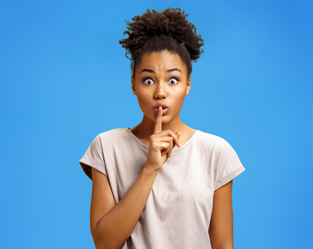Young girl holds forefinger on lips, has mysterious expression, shows silence gesture. Photo of african american girl wears casual outfit on blue background. Emotions and pleasant feelings concept.