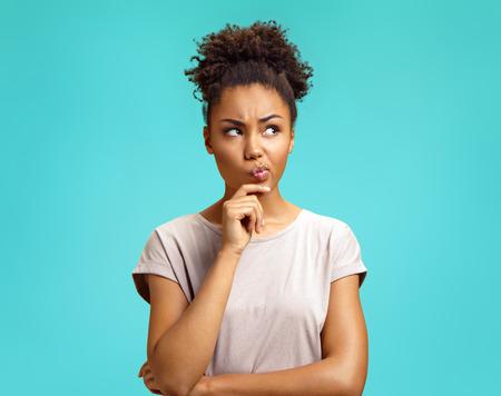 Peinzend meisje is diep in gedachten, trekt wenkbrauwen op, buigt lippen, houdt kin vast. Foto van Afro-Amerikaans meisje draagt een casual outfit op een turkooizen achtergrond. Emoties en aangename gevoelens concept.