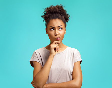 Pensive girl being deep in thoughts, raises eyebrows, curves lips, holds chin. Photo of african american girl wears casual outfit on turquoise background. Emotions and pleasant feelings concept.