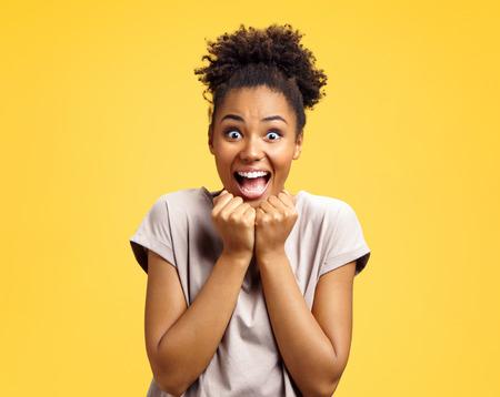 La ragazza felice guarda con gioia la telecamera, tiene le mani insieme sotto il mento. La foto della ragazza afroamericana indossa un abbigliamento casual su sfondo giallo. Emozioni e sensazioni piacevoli concetto.
