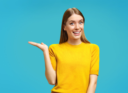 Smiling young girl points aside her open palm, shows copy space for your advert. Photo of attractive girl in yellow sweater on blue background. Stock Photo
