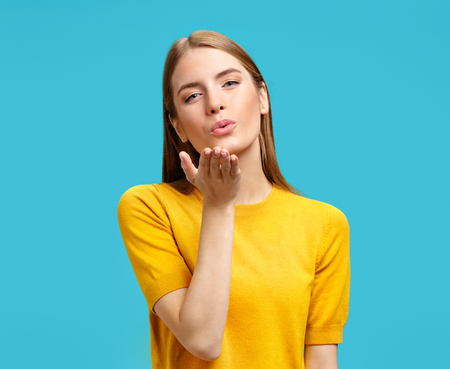Cute girl blows kiss at camera, demonstrates love or says goodbye on distance. Photo of girl in yellow sweater on blue background Standard-Bild - 119981708