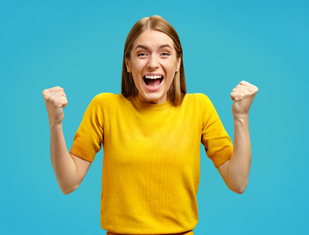Excited girl with widely open mouth holds hands clenched in fists, exclaimed with positiveness. Photo of attractive girl in yellow sweater on blue background. Emotions and pleasant feelings concept.