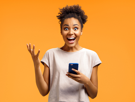 Amazed girl holds smartphone, happy to receive notification, gestures actively from happiness. Photo of african american girl on orange background. Emotions and pleasant feelings concept Foto de archivo - 119981717