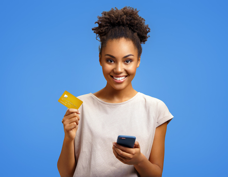 Smiling girl holds smart phone and credit card. Photo of african american girl wears casual outfit on blue background. Emotions and pleasant feelings concept. Reklamní fotografie - 120344454