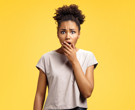 Young girl covers her mouth with shock, being frightened by something. Photo of african american girl wears casual outfit on yellow background. Emotions and Omg concept Banque d'images