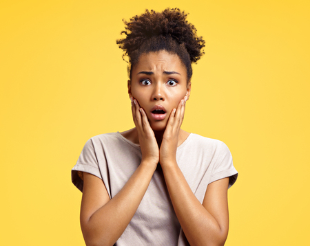 Astonished girl with big eyes, opens mouth widely, keeps hands on cheeks. Photo of african american girl wears casual outfit on yellow background. Emotions and Omg concept 스톡 콘텐츠