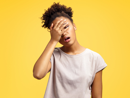 Tired girl covers face with hand, stress. Photo of african american girl wears casual outfit on yellow background. Emotions and Omg concept