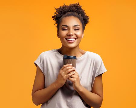 Junges Mädchen hält heißen Kaffee zum Mitnehmen, schließt die Augen vor Vergnügen. Foto des afroamerikanischen Mädchens trägt lässiges Outfit auf orangefarbenem Hintergrund. Emotionen und angenehmes Gefühlskonzept.