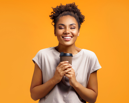 Young girl holds hot takeaway coffee, closes eyes from pleasure. Photo of african american girl wears casual outfit on orange background. Emotions and pleasant feelings concept.