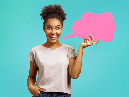 Smiling girl holds pink speech bubble banner. Photo of african american girl wears casual outfit on turquoise background. Emotions and pleasant feelings concept. Stock Photo