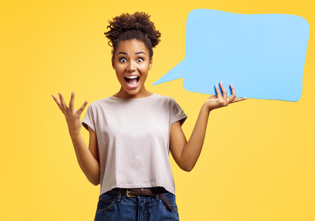 Overjoyed girl holds blue speech bubble board. Photo of african american girl wears casual outfit on yellow background. Emotions and pleasant feelings concept.