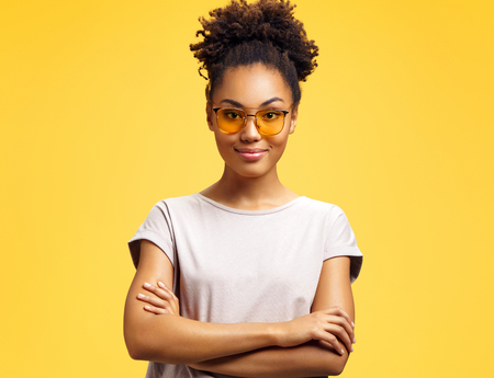 Confident girl holds hands crossed, wears sunglasses. Photo of african american girl wears casual outfit on yellow background. Emotions and pleasant feelings concept. Stock Photo