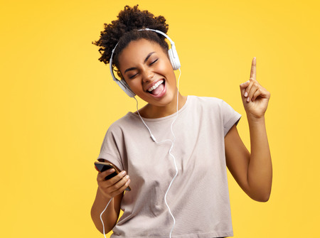 Cheerful young girl in headphones, dance actively. Photo of african american girl wears casual outfit on yellow background. Emotions and pleasant feelings concept. 写真素材