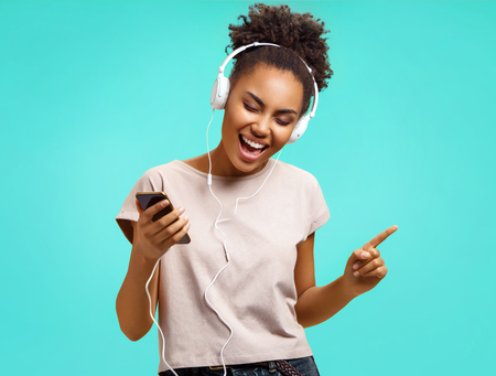Joyful girl listens song and sings, gestures and closes eyes. Photo of african american girl wears casual outfit on turquoise background. Emotions and pleasant feelings concept.