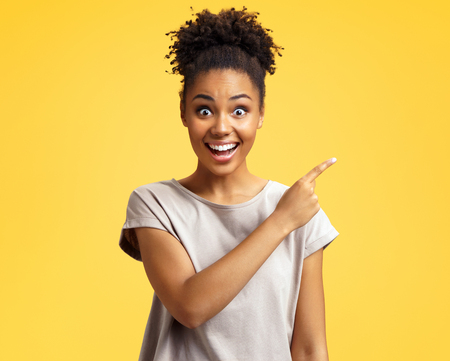 Overjoyed girl points aside, shows something at freespace. Photo of african american girl wears casual outfit on yellow background. Emotions and pleasant feelings concept.