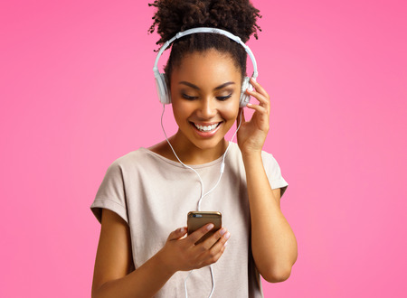 Happy young girl listens music in headphones. Photo of african american girl wears casual outfit on pink background. Emotions and pleasant feelings concept. 写真素材