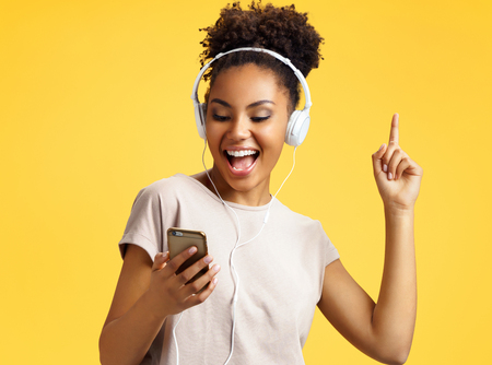 Cheerful young girl in headphones, dance actively. Photo of african american girl wears casual outfit on yellow background. Emotions and pleasant feelings concept. Stock fotó
