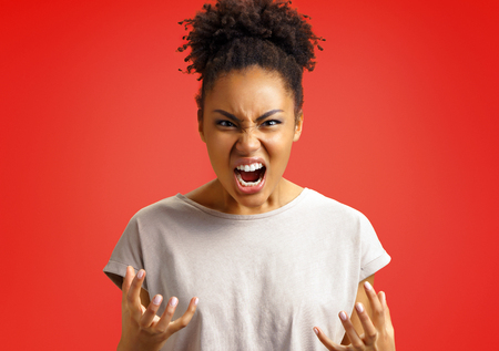 Annoyed girl gestures and shouts in anger. Photo of african american girl wears casual outfit on red background. Emotions and pleasant feelings concept. 写真素材