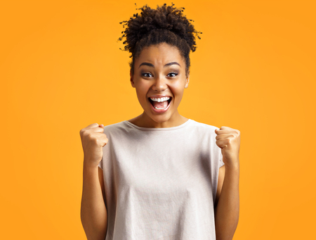 Overjoyed girl clenches fists with happiness, widely opens mouth as shouts loudly. Photo of african american girl wears casual outfit on orange background. Emotions and pleasant feelings concept.