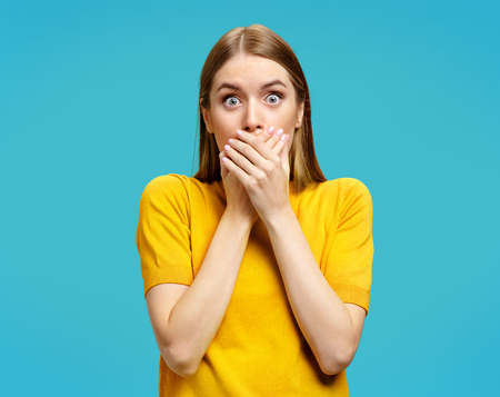 Stunned young girl closes her mouth with her hands, looks at camera. Photo of attractive girl in yellow sweater on blue background Stock Photo