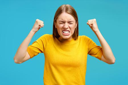 Fille d'agression avec la bouche largement ouverte et les dents serrées tient les mains serrées dans les poings. Photo de fille en pull jaune sur fond bleu. Concept d'émotions et de sentiments