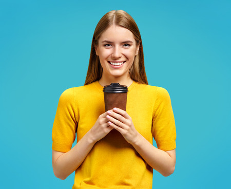 Young girl holds paper cup with hot coffee, takeaway. Photo of attractive girl in yellow sweater on blue background 写真素材