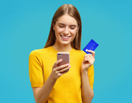 Happy girl looks at the phone and holds credit card. Photo of beautiful girl in yellow sweater on blue background. Emotions and pleasant feelings concept